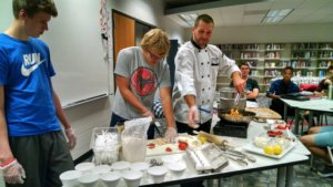 dcg students learning to cook from a chef